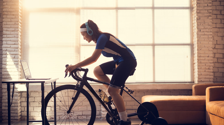 woman working out at home on her bike