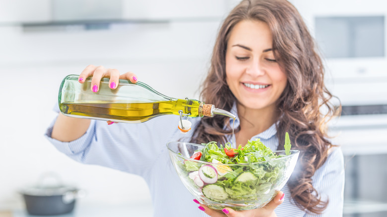 woman pouring olive oil on salad