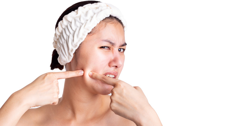 Young woman popping skin on face