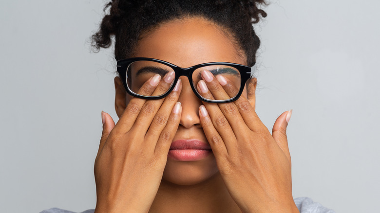 woman holding fingers against eyes