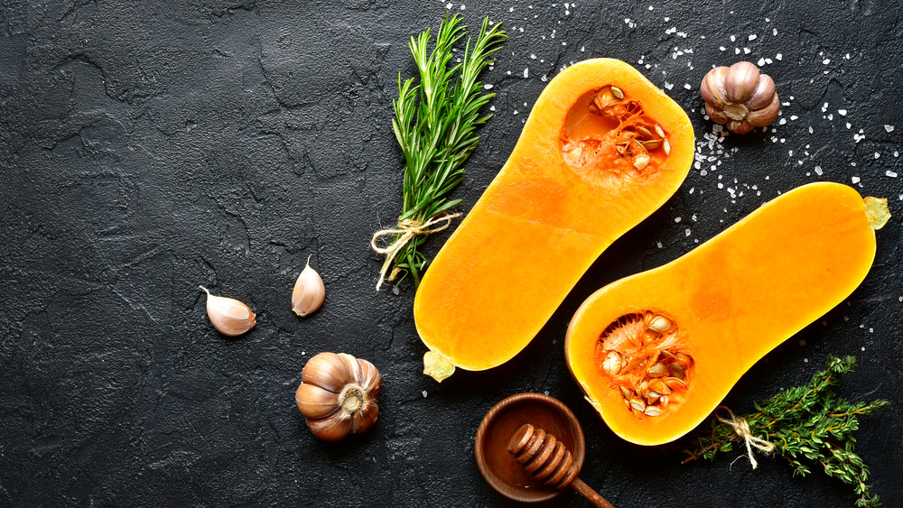 Butternut squash sliced in half with garlic and thyme