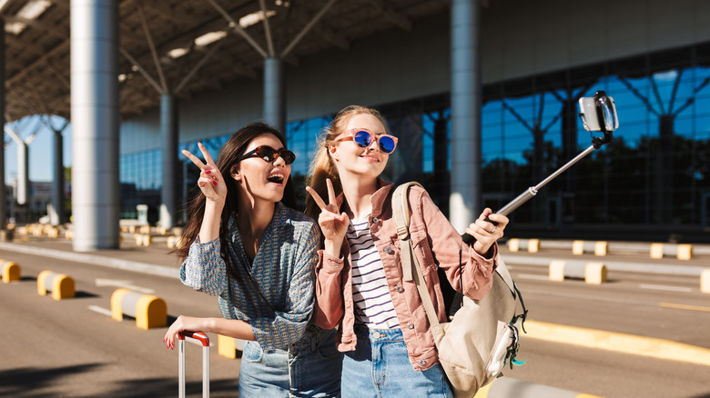Two women wearing sunglasses at airport