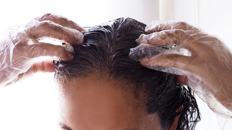 woman wearing protective gloves while applying hair dye