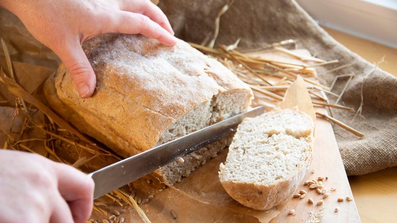 Person slicing fresh bread on a cutting board