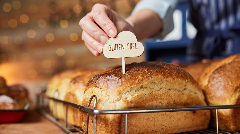 Someone puts a gluten free sign into a loaf of bread