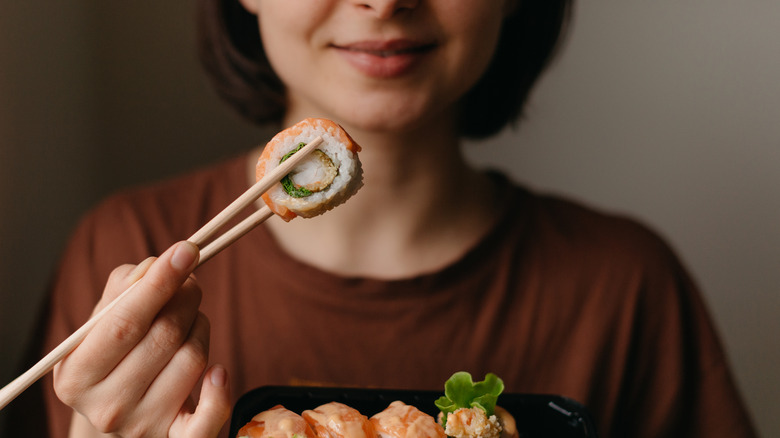Woman holding sushi with chopsticks