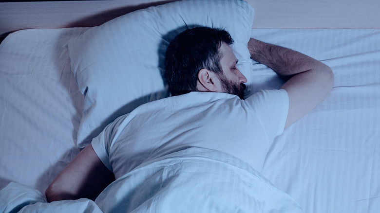 Man sleeping on his stomach in bed