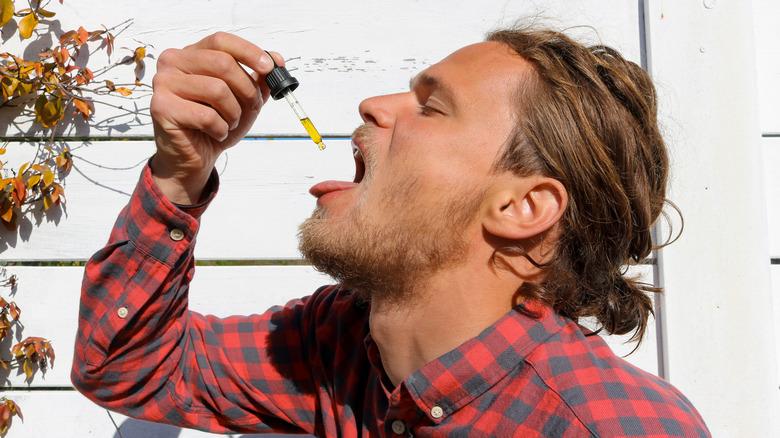 caucasian male taking cbd oil