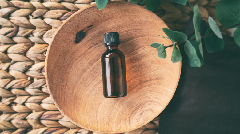 A bottle of essential oil in a wooden bowl