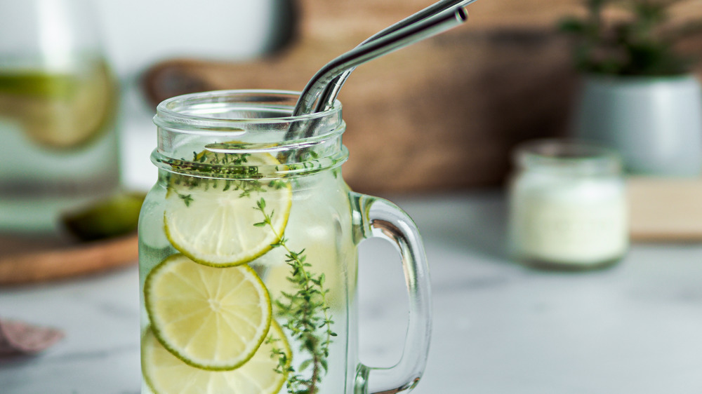 Lime infused water in mason jar glass with straws