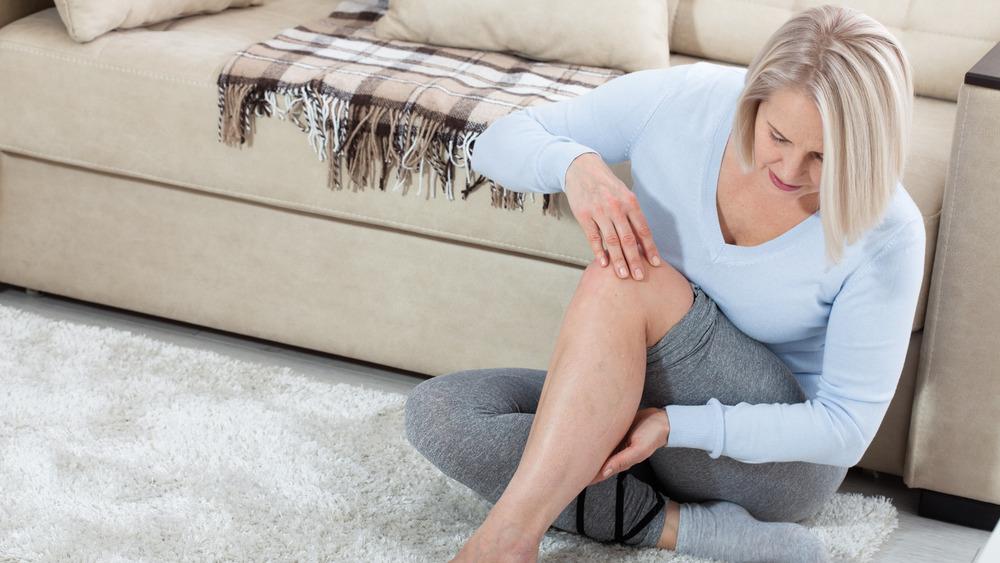 Woman holding sore leg