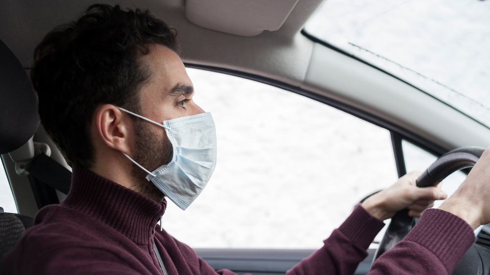Man with beard driving with mask on