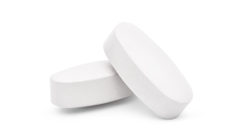 close up of two calcium pills with an all white background
