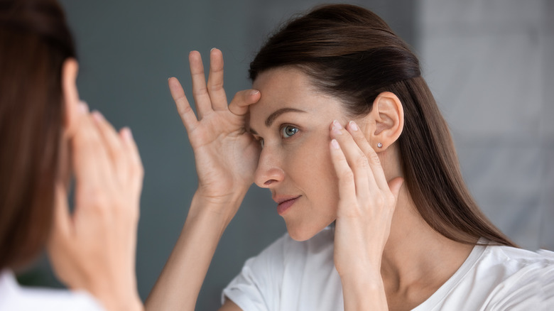 woman inspecting face