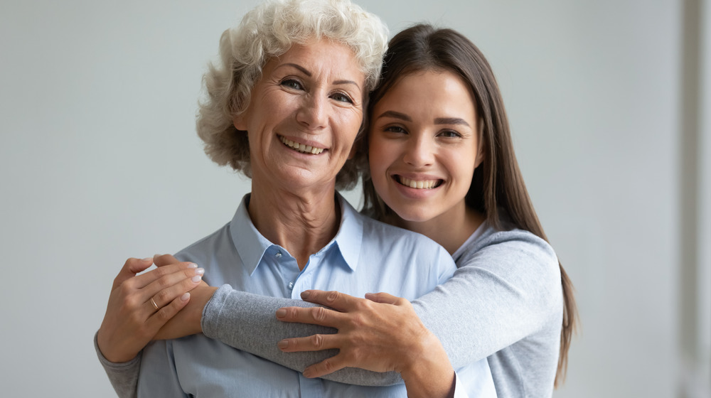 mother and daughter smiling, hugging