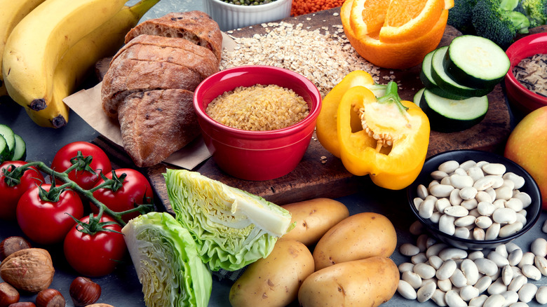 A collection of foods rich in carbs with bread, grains, and pieces of peppers, oranges, and cucumbers in the center