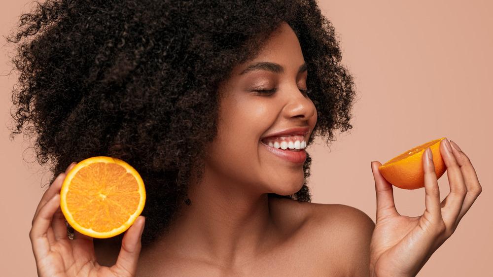 smiling woman holding orange halves