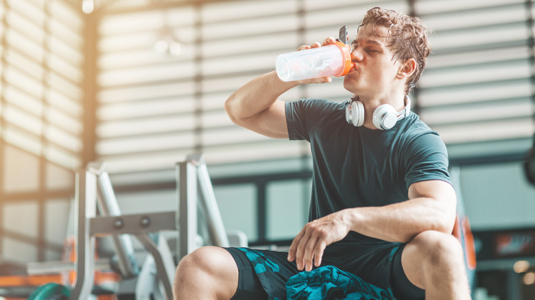 A man takes a pre-workout supplement before exercise