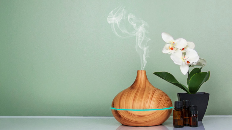 essential oil diffuser with oils, orchid and green background